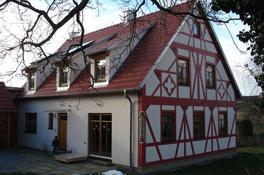 Das Haus ist fertig! Holzrahmenbauweise mit sichtbarem Dachstuhl, Außenwände z. T. verputzt, z. T. vorgeblendetes Fachwerk